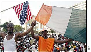Men wave the US and Ivorian flags outside the US embassy