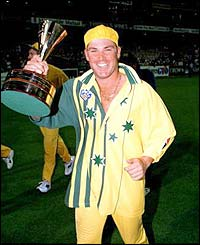 Shane Warne grins and holds the trophy as Australia celebrate winning the World Series in 1995
