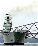 HMS Ark Royal as it leaves Rosyth under the Forth bridge in Fife, Scotland