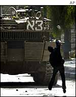 Palestinian boy throws stone at Israeli tank in Hebron