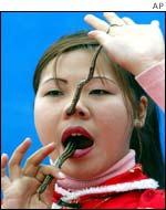 A woman threads a live snake up her nose in Beijing