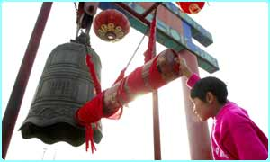 A girl ringing a bell inpreparation for Chinese new year