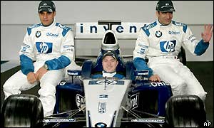 Drivers Juan Montoya and Ralf Schumacher pose alongside test driver Marc Gene as the new car is launched