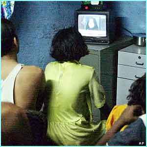 A family in Bombay sit in front of a TV to watch the news about Columbia
