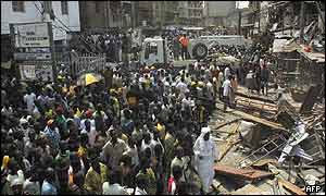 Crowds gather outside the devastated buildings on Lagos Island