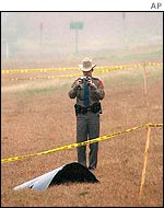 Texas policeman photographs a piece of shuttle debris