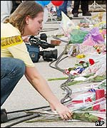 A girl lays flowers in Nacogdoches