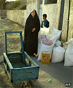 Iraqi woman stands next to her family's food allocation for two months