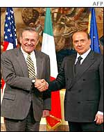 Donald Rumsfeld (left) shakes hands with Italian Prime Minister Silvio Berlusconi (right)