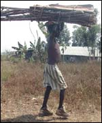 A displaced boy carries material to build a hut in the camp