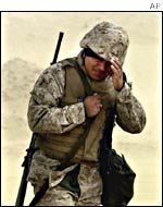 A US marine walks during a sand storm in the Kuwaiti desert on  Feb. 3, 2002