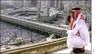 A Saudi security man looks on from a roof top as Muslim pilgrims gather inside and outside the grounds of the holy Kaaba