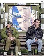 Montenegrins sit in front of election posters