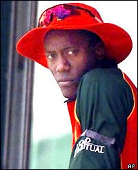 Zimbabwe's Henry Olonga wears a black armband to protest against the government as he sits watching his team bat