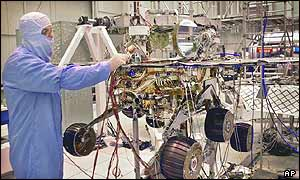 Engineer stands next to a nearly fully-assembled Mars Exploration rover