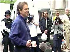 Prime Minister Tony Blair, paternal mug in hand, relaxes in front of the media