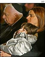 Rona Ramon, wife of Israeli astronaut Ilan Ramon holds their daughter Noah while sitting alongside Israeli Prime Minister Ariel Sharon during a state ceremony, 10 February 2003
