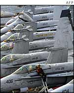 A US navy plane captain sits on the wing of an F/A-18 Hornet aboard the USS Abraham Lincoln,