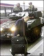 A passenger passes in front of UK troops at Heathrow airport