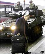 A passenger walks in front of troops at Heathrow