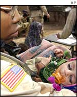 US soldier cradles a malnourished infant during a humanitarian aid medical mission in Makwan Afghanistan