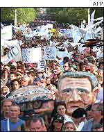 Caricatures of John Howard and George W Bush are carried by protestors