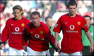A dejected Man Utd skipper Roy Keane (right) is followed off the pitch by Nicky Butt and Diego Forlan