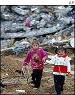 Children walk in front of demolished houses in Beit Lahiya