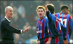 Referee Dermot Gallacher is surrounded by protesting Crystal Palace players