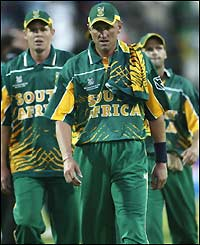 Allan Donald leads his dejected South African team-mates off the pitch