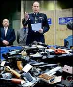 Sir John Stevens shows weapons collected during a guns amnesty