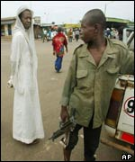 A man looks disapprovingly at a young rebel in Bouake