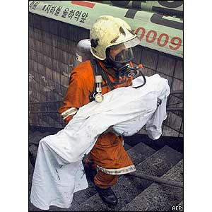 A firefighter carries a body from the subway