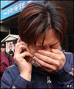 A woman cries as she makes a phone call after the South Korean subway fire