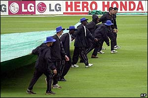 Ground workers pull the covers over the pitch as the match is abandoned