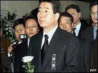 South Korean President-elect Roh Moo-Hyun (C) stands with a carnation in front of an altar