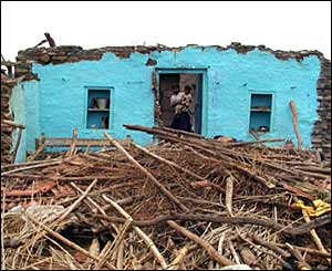 A villager in Madhya Pradesh stands by the remains of her home after floods devastated the area
