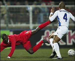 Emile Heskey falls to the floor after a challenge from Alain Boumsong