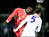 Auxerre's Philippe Mexes challenges Liverpool's Emile Heskey for the ball