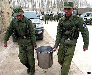 Two Chinese soldiers carry a vat of soup to earthquake victims