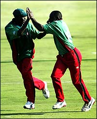Maurice Odumbe (left) celebrates one of his four wickets with Tony Suji of Kenya