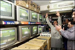 Pakistani cricket fans watching the game on television in Lahore celebrate at Saeed Anwar reaches his fifty