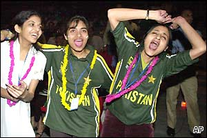 Three young Pakistan fans walk down the street after their team's defeat
