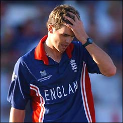 England's James Anderson holds his head in his hand as Andy Bichel smashes him for six