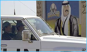 UN weapons inspectors drive past a portrait of Saddam Hussein