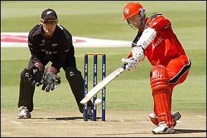 Canada opener John Davison smashes the ball to the boundary on the way to 50