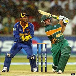 South African batsman Mark Boucher hits a six as the rain pours down