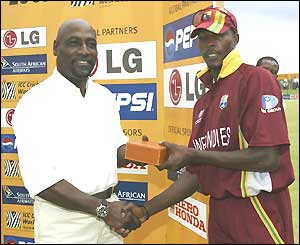 The West Indies' Vaspert Drakes (right) receives the man-of-the-match award after career-best bowling figures of 5-33
