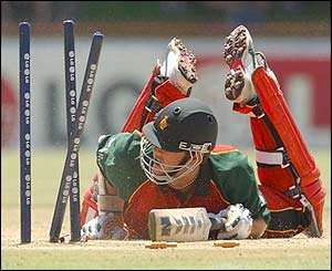 Zimbabwe's Andy Blignaut lays on the pitch after being run out