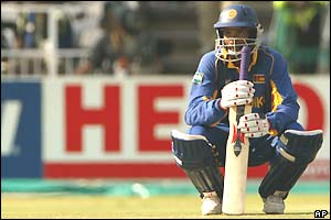 Russel Arnold crouches down holding his bat at the non-striker's end